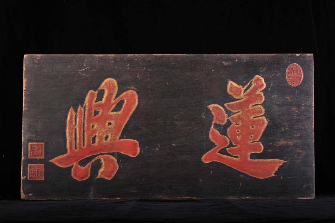Carved wood panel with red and gilt painted symbols