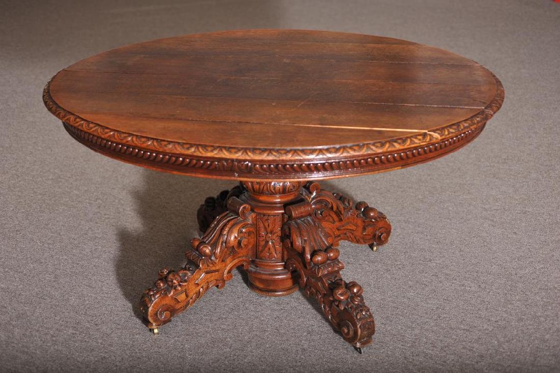 Heavily carved oak oval topped dining table, raised on