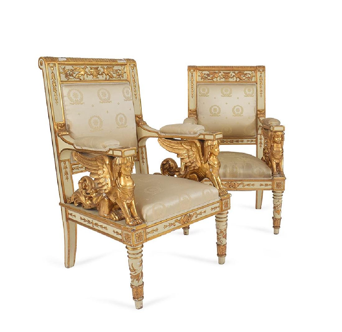 A pair of white lacquered and gilt-wood armchairs