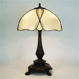 A patinated bronze table lamp with ivory glass