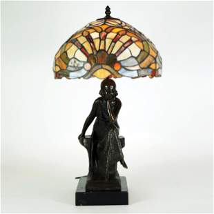 A patinated bronze table lamp with polychrome glass