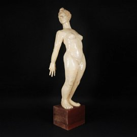 A white ceramic figure of a naked woman
