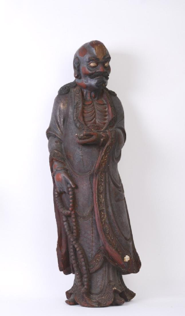 A Chinese wood carved and Da Mo figure