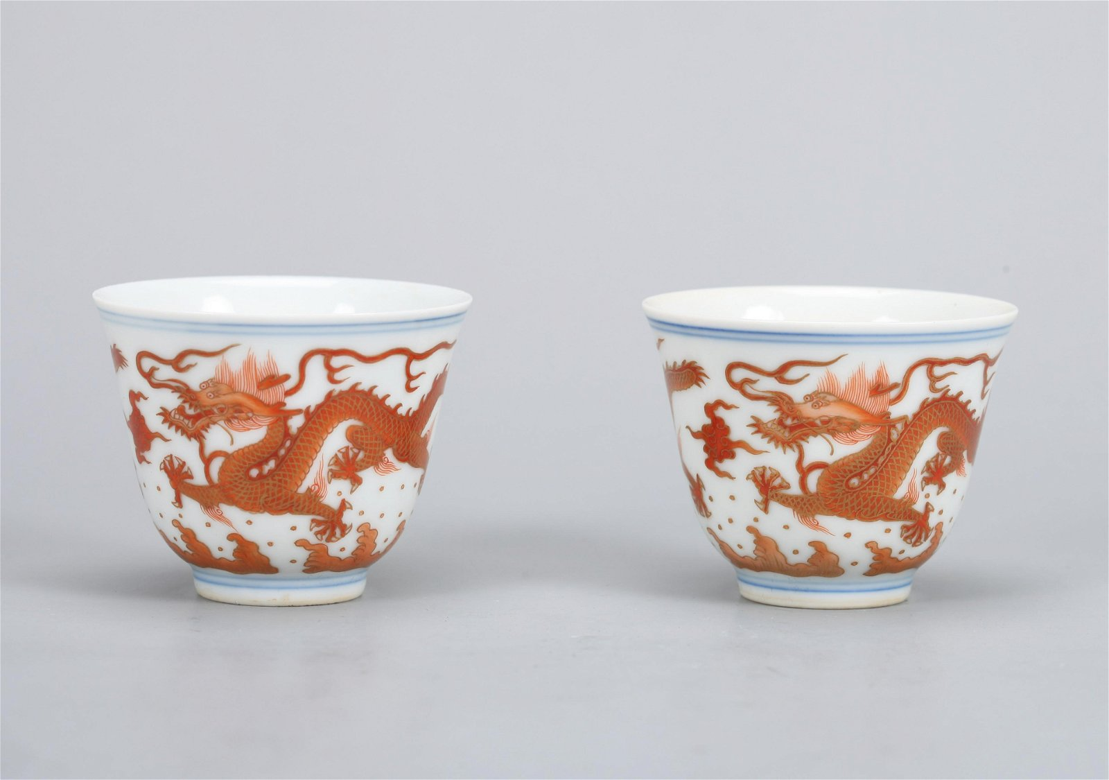 A PAIR OF CHINESE GILT-DECORATED IRON-RED CUPS,