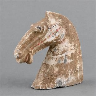 A PAINTED EARTHENWARE HORSE HEAD