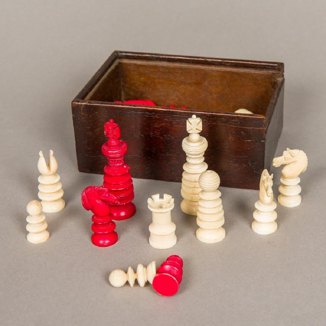 A Victorian English carved ivory chess set Housed in a