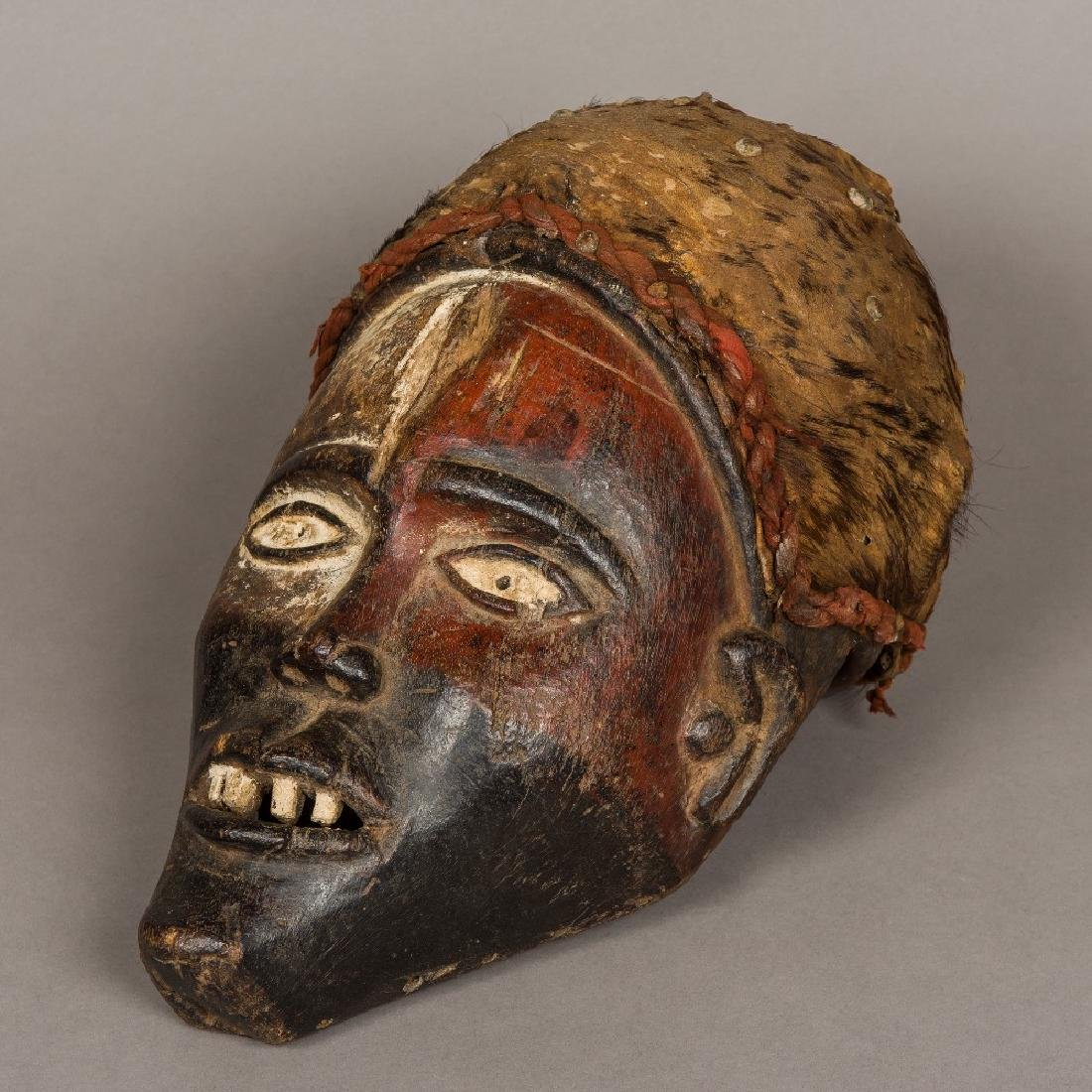 An African carved wooden tribal mask Mounted with a