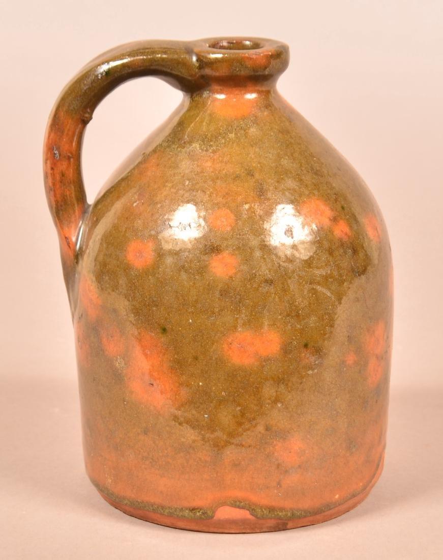 New England 19th Century glazed Redware Qt. Size Jug.