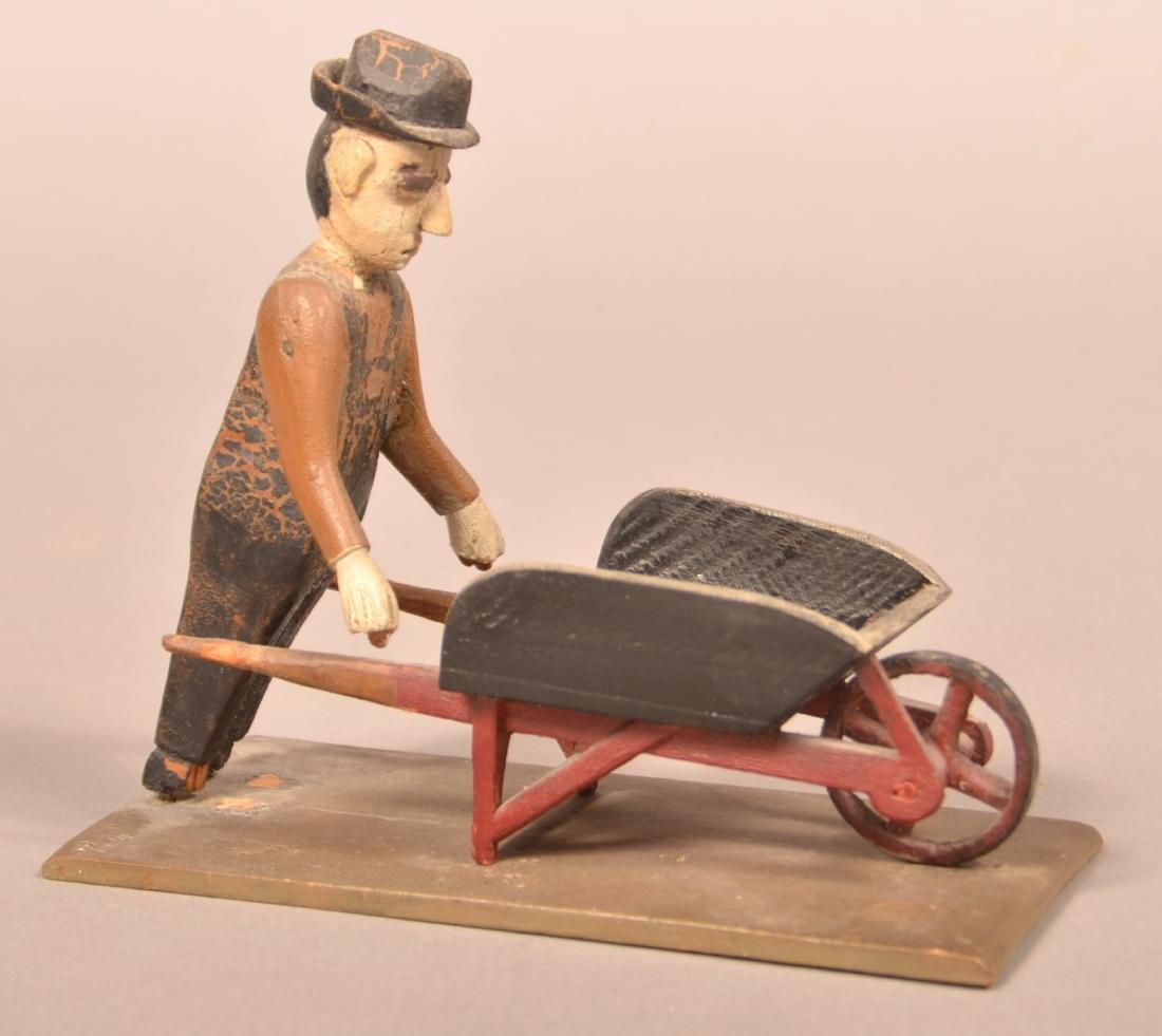 Folk Art Carving of a Man with Wheel Barrow.