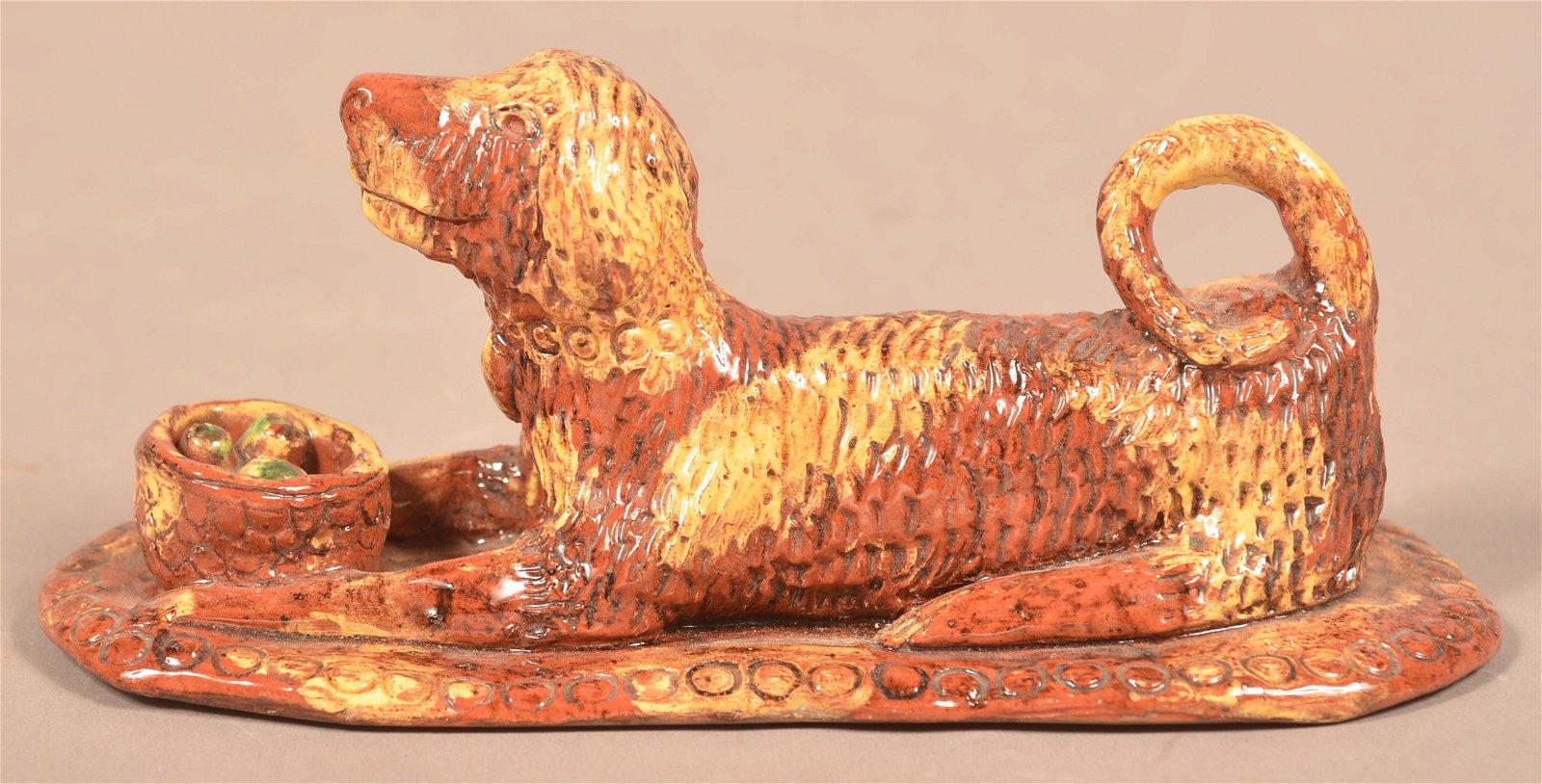 Glazed Redware Figure of a Recumbent Dog with Basket.