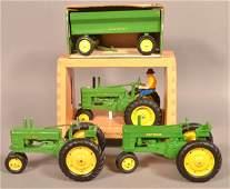 Three various John Deere Tractors and a Wagon.