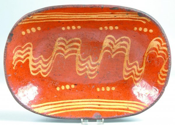448: Slip Decorated Redware Charger, oval form with cog