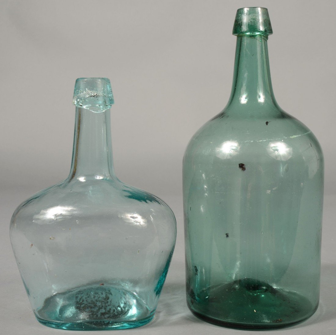 225: Two Aquamarine Blown Glass Wine Bottles. 1st is a