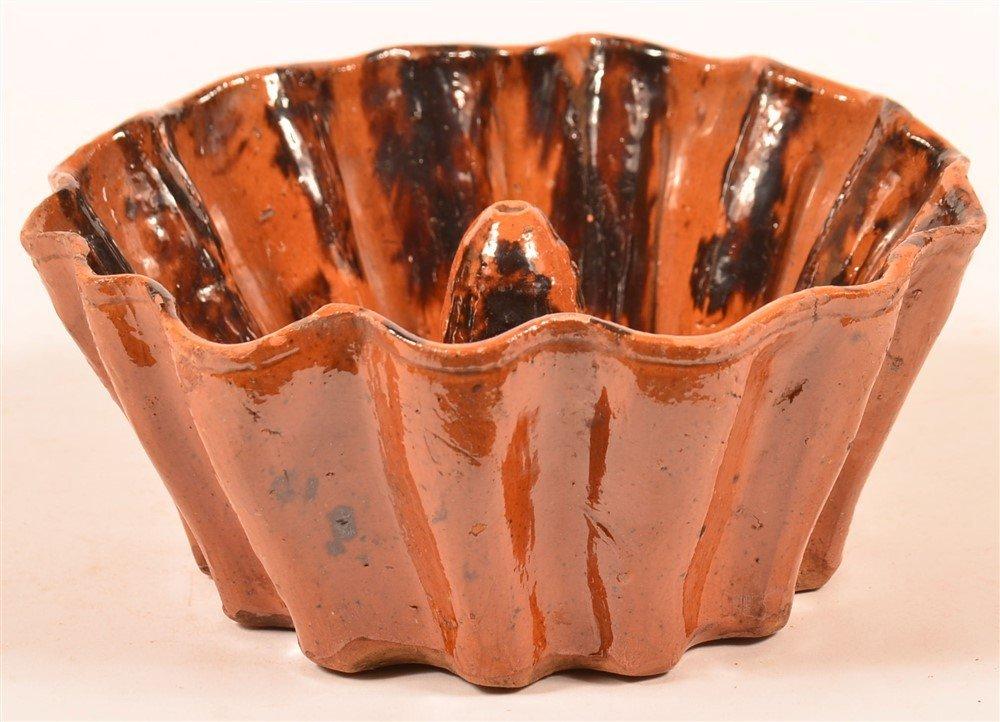 Mottle Glazed Redware Scallop Edge Turks Mold.