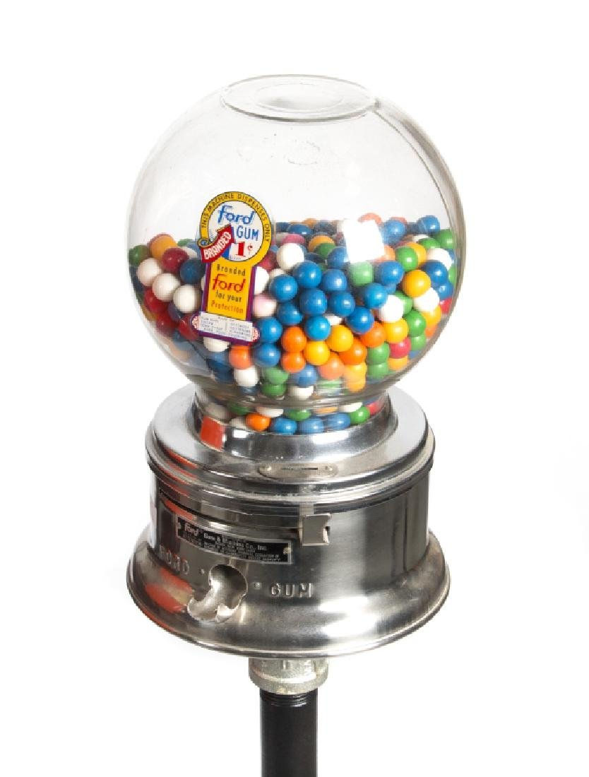 A vintage gum pack and gumball machine on stands