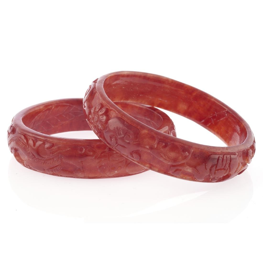 A collection of two carved jade bangle bracelets