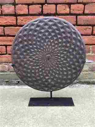 Antique Geometric Vortex Manhole Cover on Custom Stand