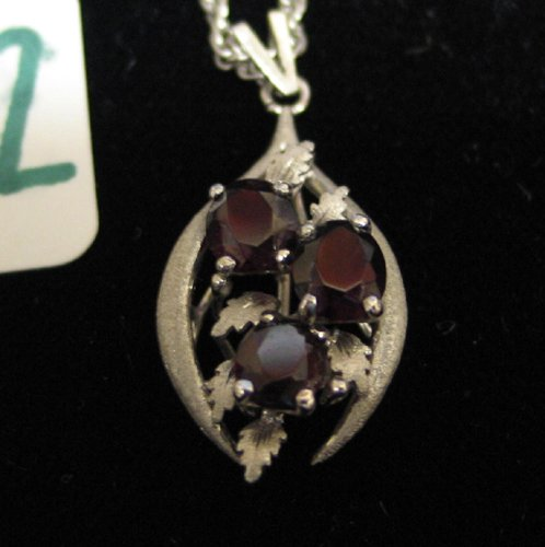 322: GARNET AND WHITE GOLD PENDANT NECKLACE. The  10K w