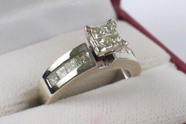 614: DIAMOND AND FOURTEEN KARAT WHITE GOLD RING. Four p