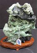 693 A CHINESE JADE FIGURAL CARVING AND STAND  The  gr