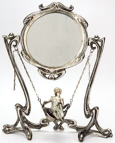 3: A SILVERED-BRONZE FIGURAL VANITY MIRROR, in the Art