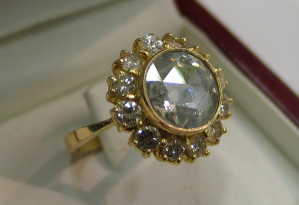 795: DIAMOND AND EIGHTEEN KARAT GOLD RING. Centered and