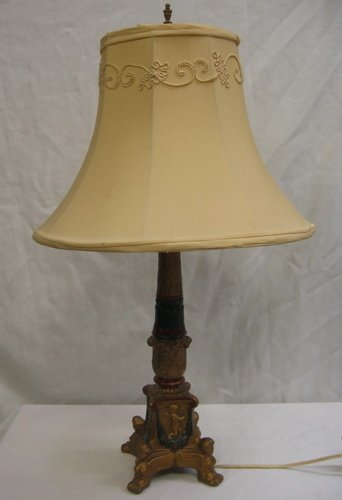 303: A COLD PAINTED IRON DESK LAMP, having gold cupids