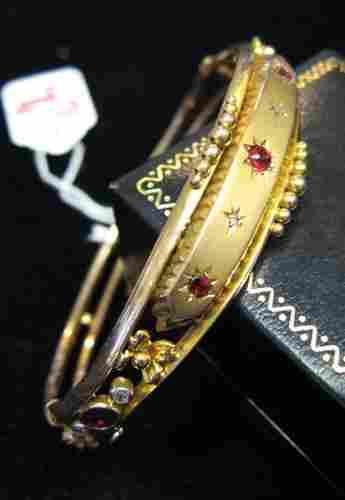 104: RUBY, DIAMOND AND NINE KARAT GOLD BANGLE, set wit