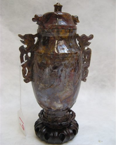 19: A SOLID AGATE COVERED JAR with stylized figural  si