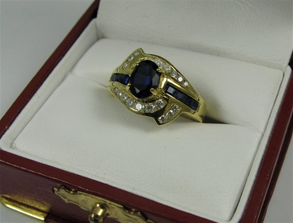 29: SAPPHIRE, DIAMOND AND 18K GOLD RING, centering  an