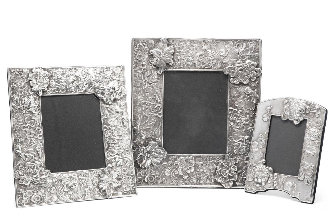 Three silver floral repousse picture frames