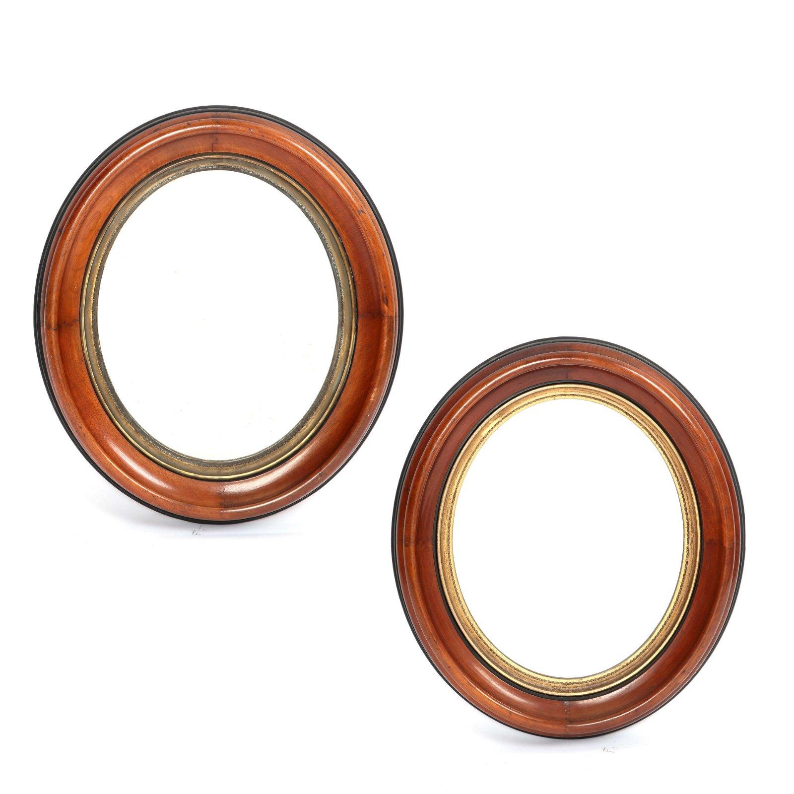 A pair of parcel gilt and ebonized walnut mirrors