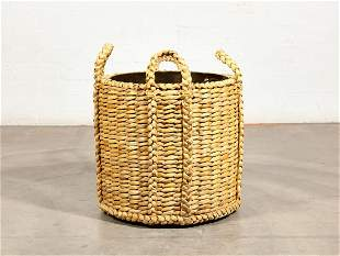 A large basket weave and brass log bin
