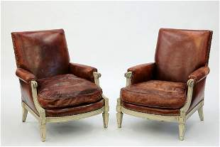 A pair of Louis XVI style brown leather bergeres