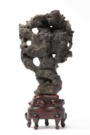 A Chinese carved stone on hardwood stand