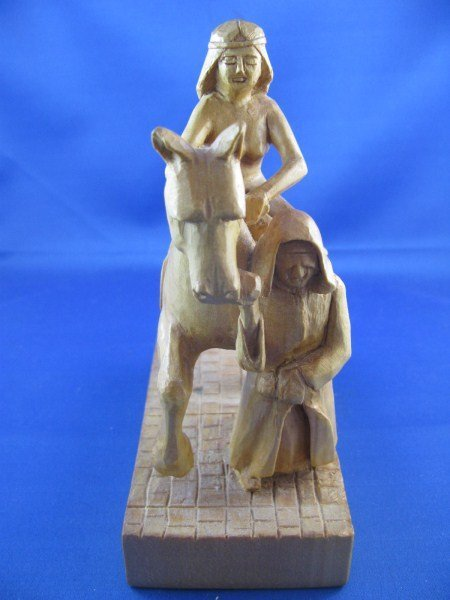 CARVING OF A MAN PULLING A HORSE WITH FEMALE RIDER