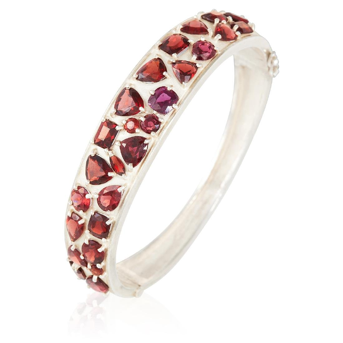 A GARNET BANGLE in sterling silver, set with round,