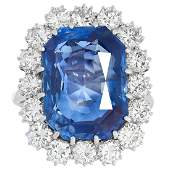 A SAPPHIRE AND DIAMOND CLUSTER RING set with a cushion