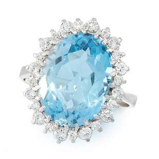 AN AQUAMARINE AND DIAMOND DRESS RING set with an oval