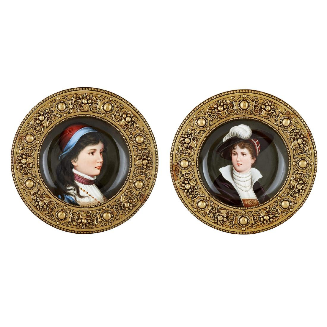 TWO AUSTRIAN CIRCULAR PAINTED PLAQUES IN BRASS FRAMES