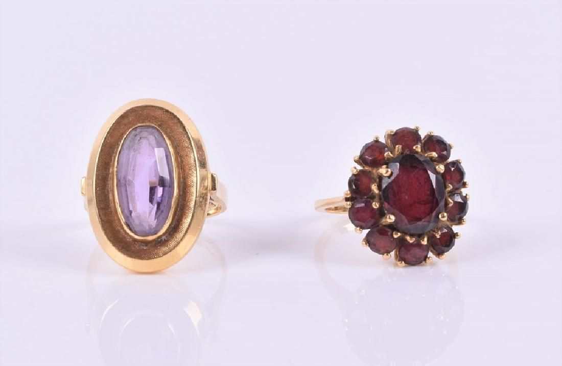 An amethyst ring the central oval amethyst within a
