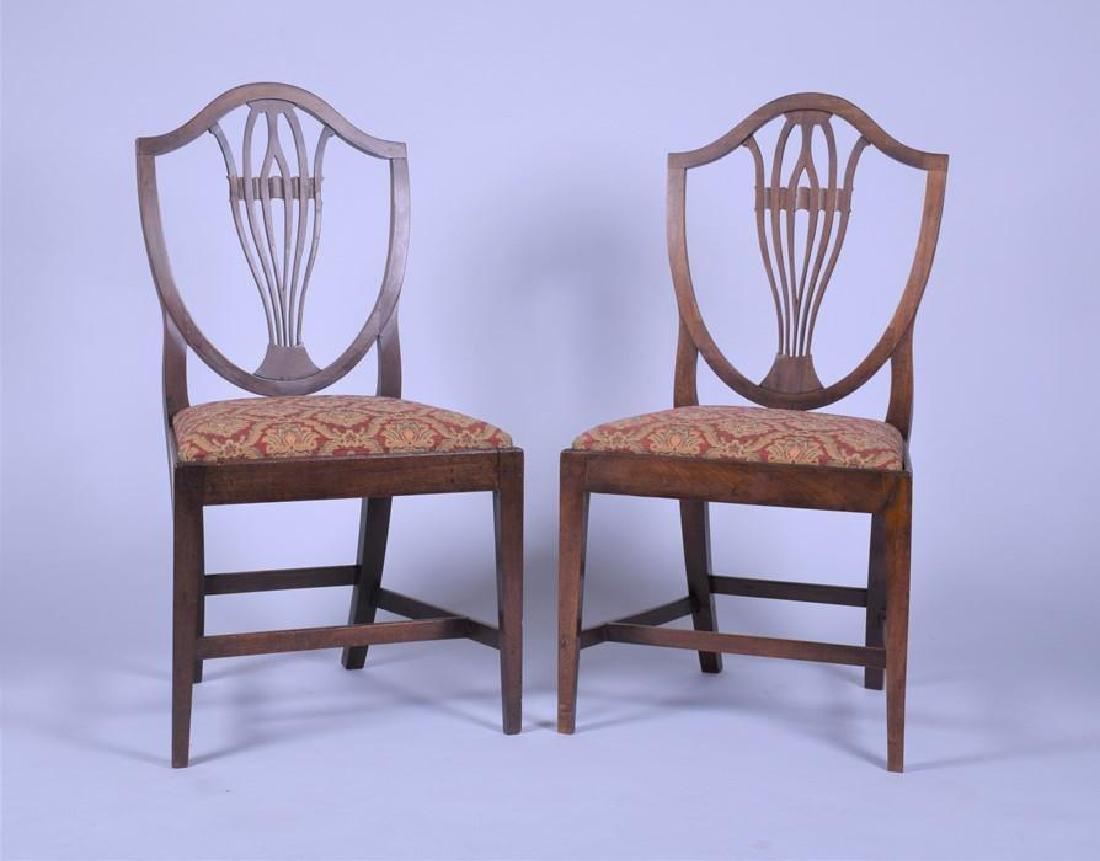 A pair of late Georgian mahogany shield back dining