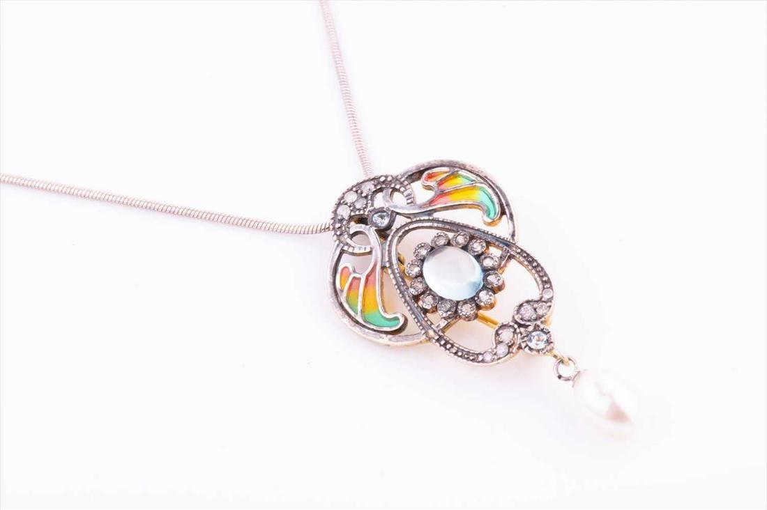 A silver, diamond, pearl, and enamel pendant / brooch
