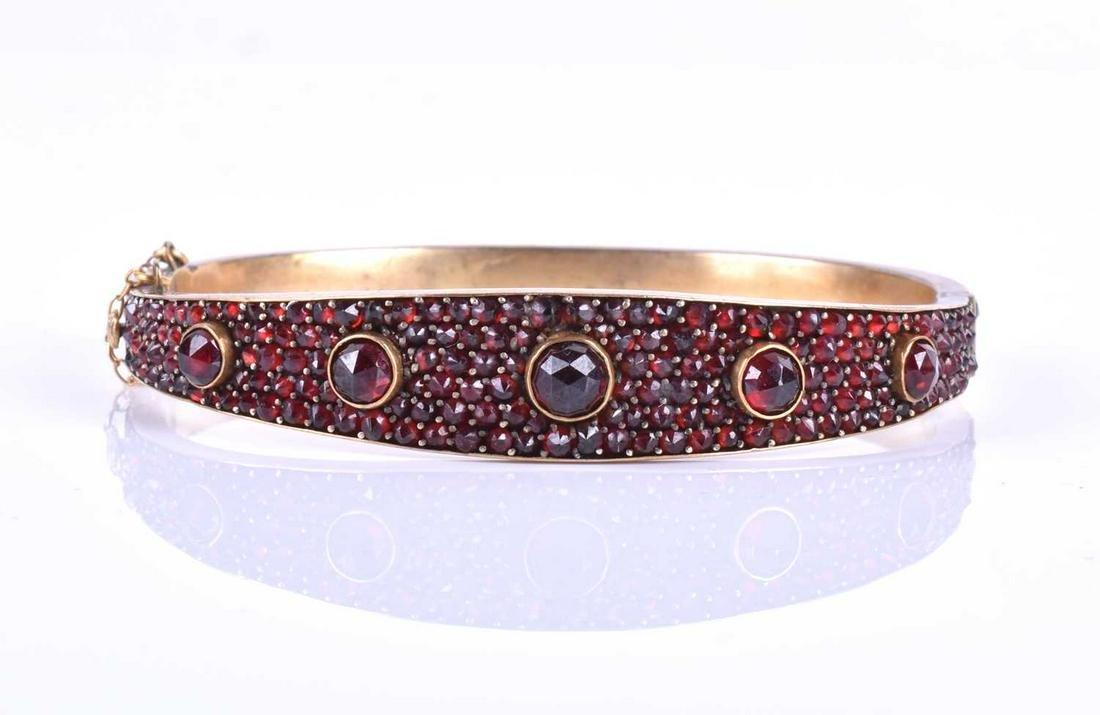 A late Victorian garnet bracelet, the gilt metal hinged