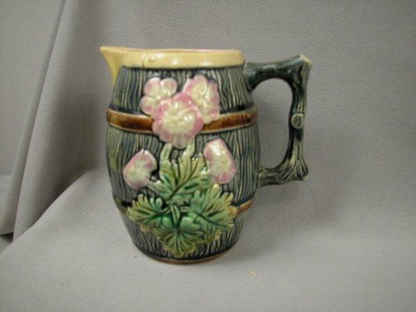 402: Majolica Barrel shaped creamer with floral motif,