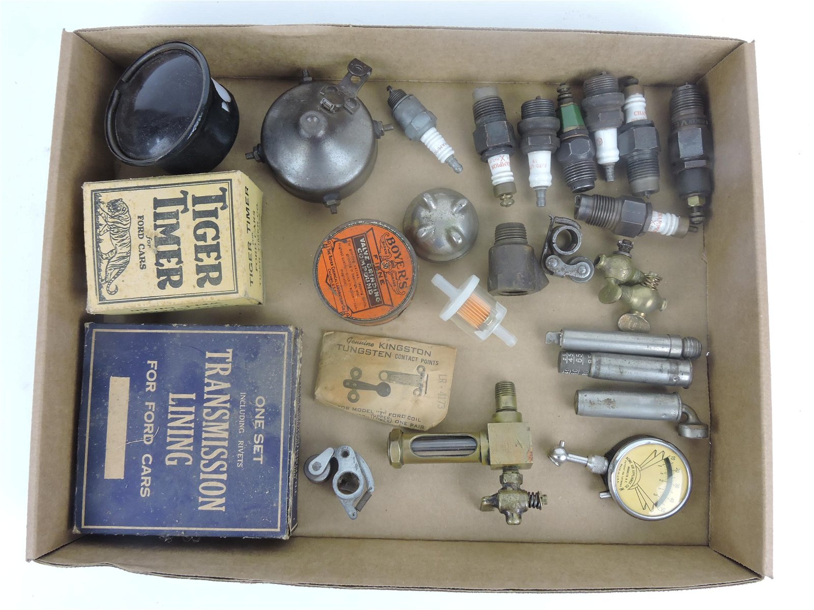 Box of old spark plugs, valves, and