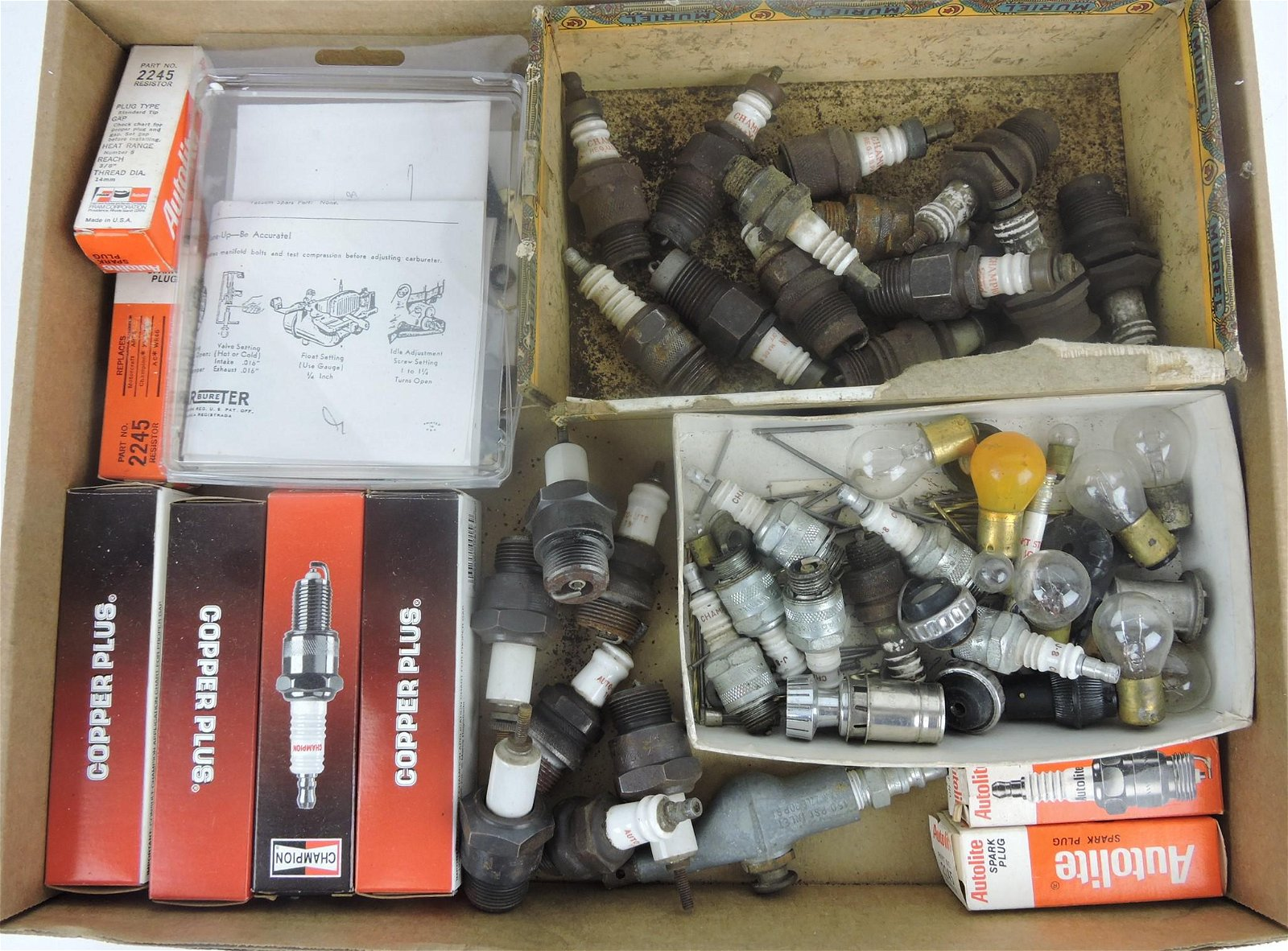 Box of old spark plugs and auto light bulbs