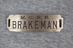 "6:  MCRR railroad at badge, ""Brakeman"""