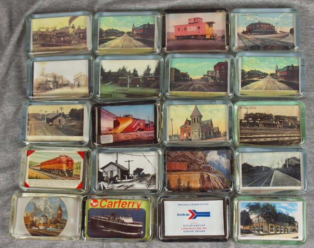 51: Lot of 20 glass paperweights with railroad related