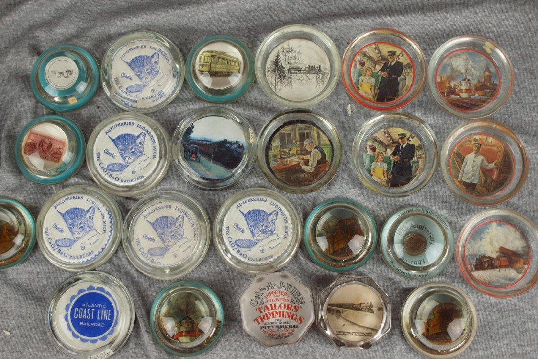 55:  Lot of 17 glass paperweights and 7 ashtrays, most
